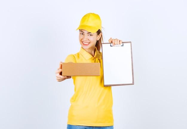 Corriere femminile in uniforme gialla che consegna il pacco di cartone e chiede di firmare l'elenco.