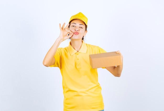 Corriere femminile in uniforme gialla che consegna un pacco di cartone e mostra con successo il segno della mano.