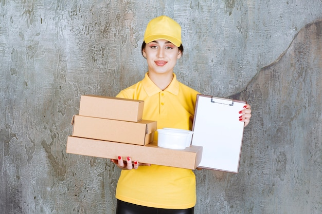 Female courier in yellow uniform delivering multiple cardboard boxes and takeaway cups and presenting the blank for signature