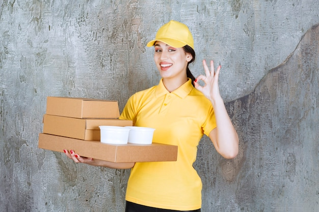 Female courier in yellow uniform delivering multiple cardboard boxes and takeaway cups and showing positive hand sign.