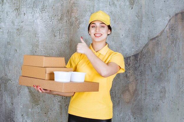 Female courier in yellow uniform delivering multiple cardboard boxes and takeaway cups and showing positive hand sign