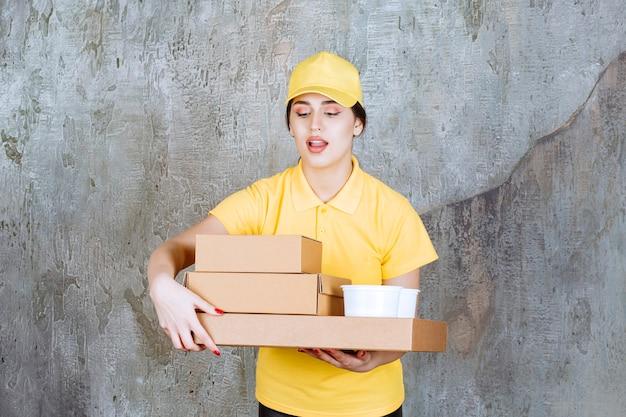 Corriere femminile in uniforme gialla che consegna più scatole di cartone e tazze da asporto