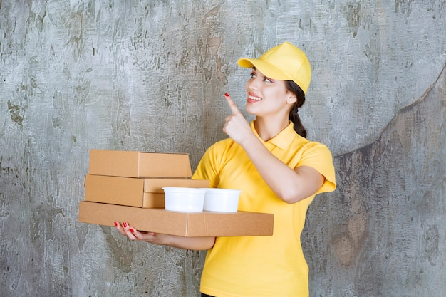 Female courier in yellow uniform delivering multiple cardboard boxes and takeaway cups.