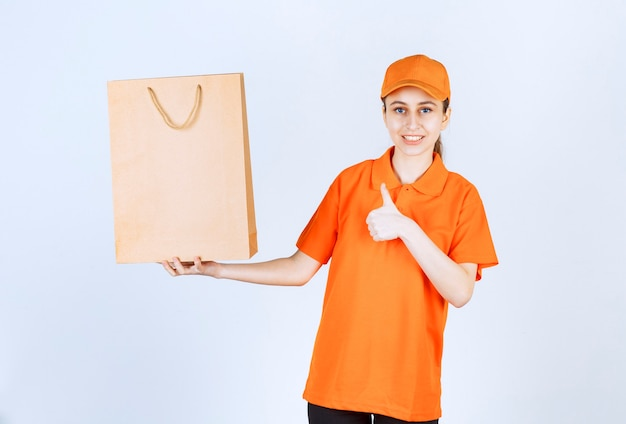 Female courier in yellow uniform delivering a shopping bag and showing positive hand sign.