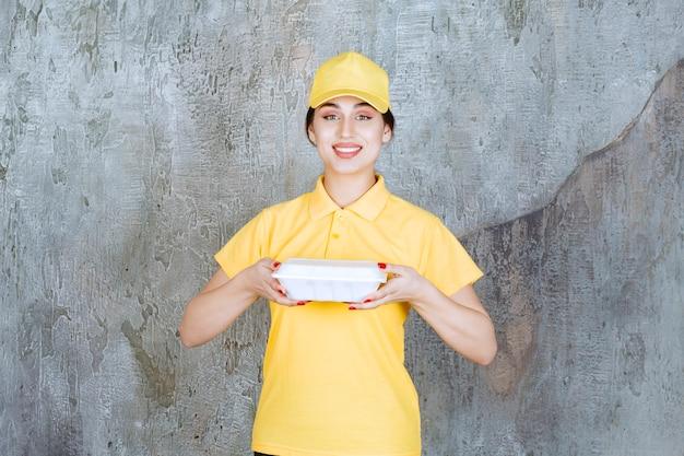 Corriere femminile in uniforme gialla che consegna una scatola bianca da asporto