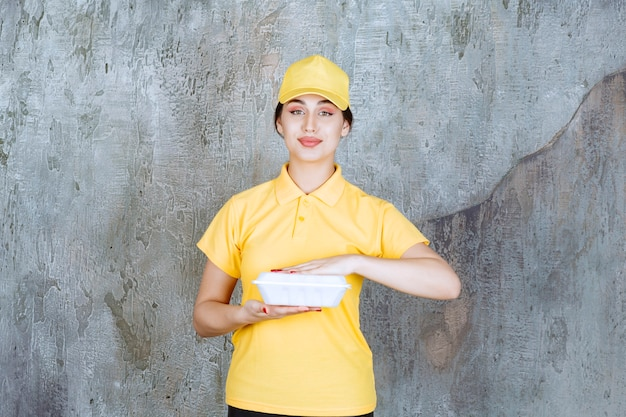 Female courier in yellow uniform delivering a white takeaway box.