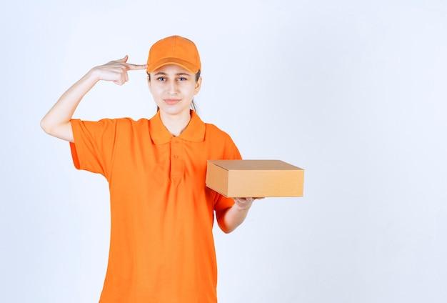 Corriere femminile in uniforme gialla che tiene una scatola di cartone e ha una buona idea.