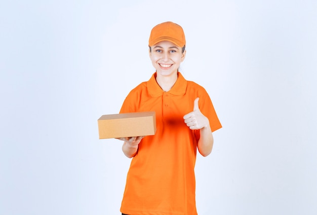 Female courier in yellow uniform holding a cardboard box and showing positive hand sign.