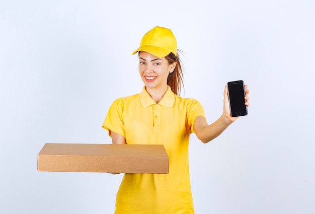 Female courier in yellow uniform holding a cardboard parcel and showing her black smartphone.