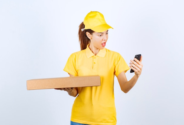Female courier in yellow uniform holding a cardboard parcel while checking her phone and smiling.