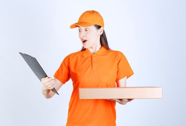 Corriere femminile in uniforme gialla che tiene in mano una scatola di cartone da asporto e controlla l'elenco degli indirizzi e sembra confuso.