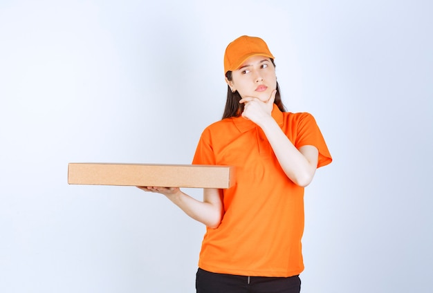 Female courier in yellow uniform holding a cardboard takeaway box, looks confused and thinking.