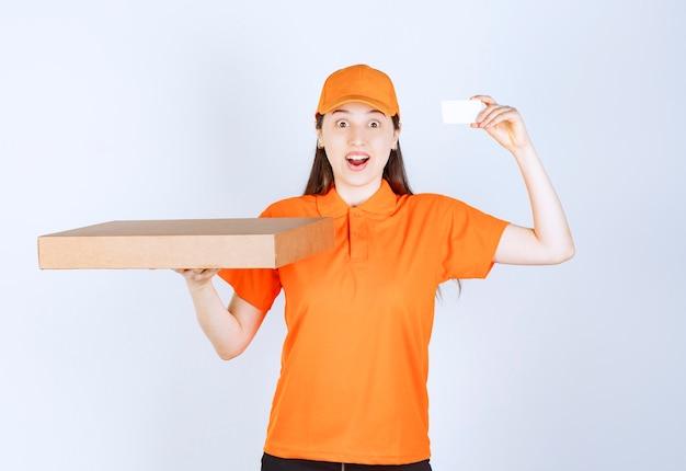 Corriere femminile in uniforme gialla che tiene una scatola di cartone da asporto e presenta il suo biglietto da visita.