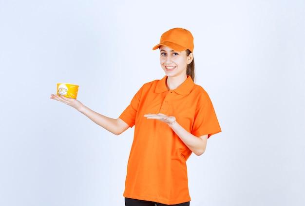 Corriere femminile in uniforme gialla che tiene una tazza di tagliatelle da asporto e indicandola.