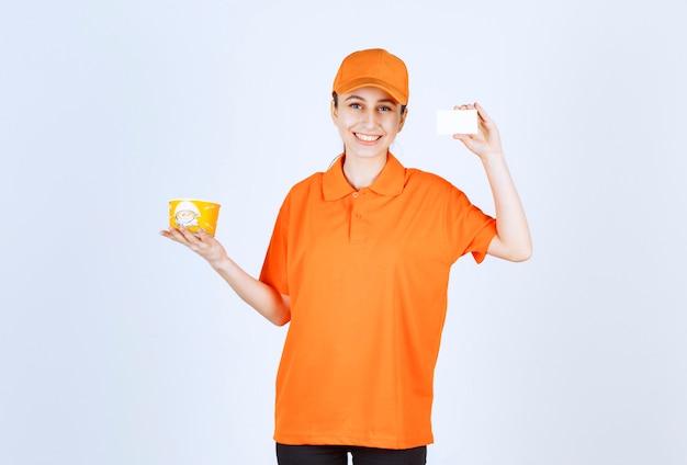 Corriere femminile in uniforme gialla che tiene una tazza di noodles da asporto e presenta il suo biglietto da visita.