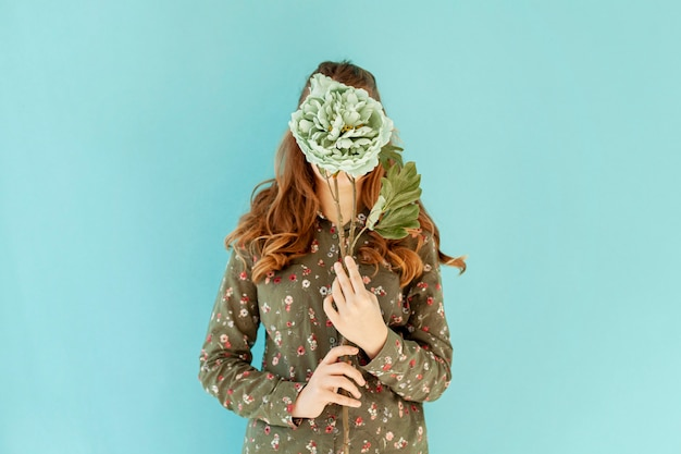 Female covering face with fresh flower