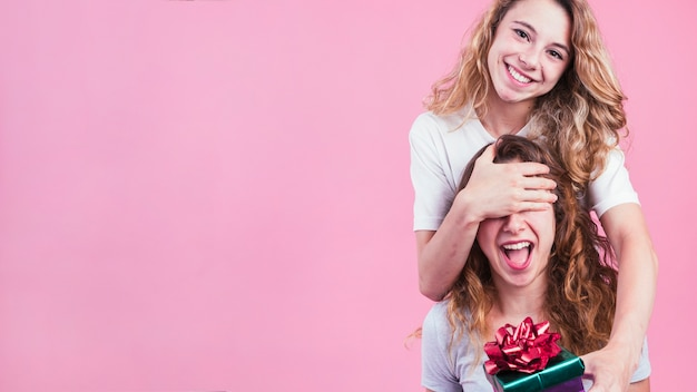 Female covering her friend's eyes giving gift box against pink background
