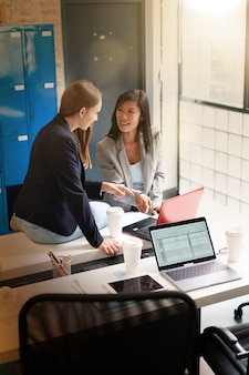 Female coworkers discussing presentation ideas in modern office