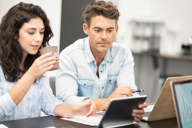 コンピューターとコワーキングする女性の同僚、成熟した男性と若い白人の女の子