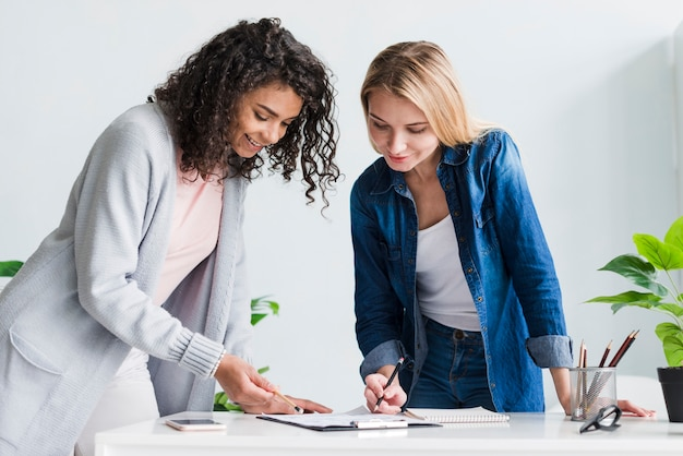 Female coworkers leaning over desk discussing project