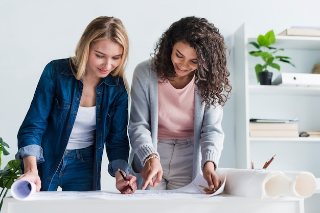 Female coworkers leaning over paper floor plan drawing