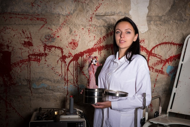 Female crazy scientist holding a severed hand and eyeball in a box in front of a blood splattered wall, halloween concept