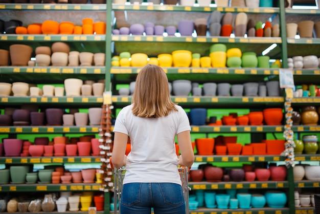 植木鉢、背面図、ガーデニングの店と棚の女性客。花卉園芸用の店で機器を購入する女性、花卉楽器の購入