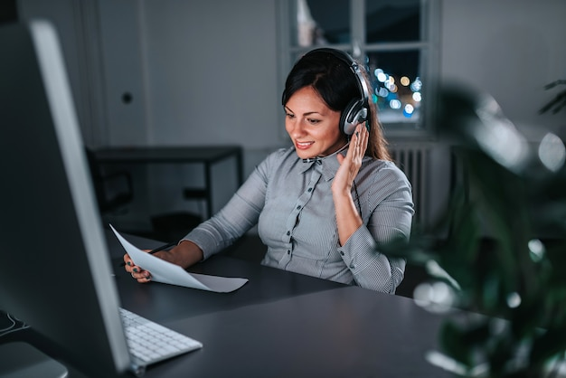 Female customer care operator working night shift in call center.