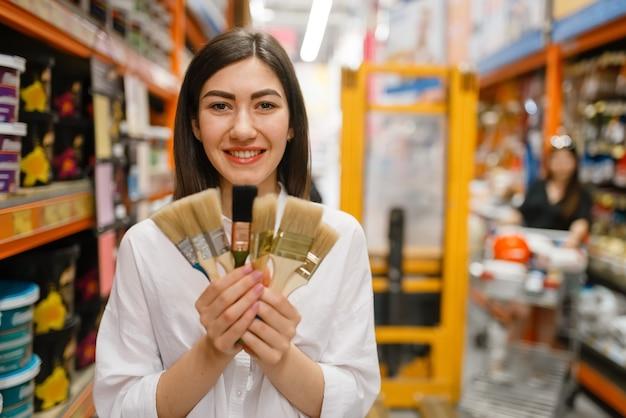 Female customer choosing brush in hardware store.