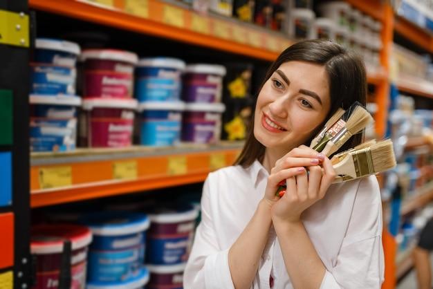 Female customer choosing brush in hardware store