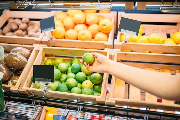 Female customer choosing fruits in food store