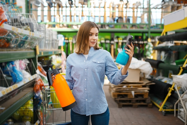 庭師のための店で庭のスプレーを選ぶ女性の顧客。花卉園芸用の店で機器を購入する女性、花卉楽器の購入