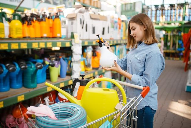 庭師のための店でガーデニングツールを選択する女性の顧客。花卉園芸用の店で機器を購入する女性、花卉楽器の購入