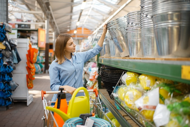 庭師のための店で金属製のバケツを選ぶ女性の顧客。花卉園芸、花卉楽器の購入、ガーデニングのために店で機器を購入する女性