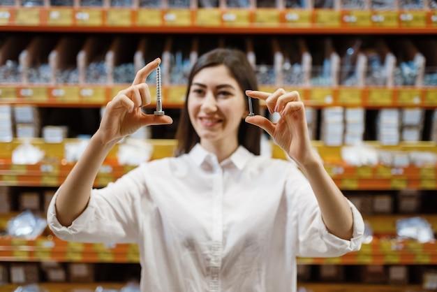 Female customer choosing tapping screw in hardware store.