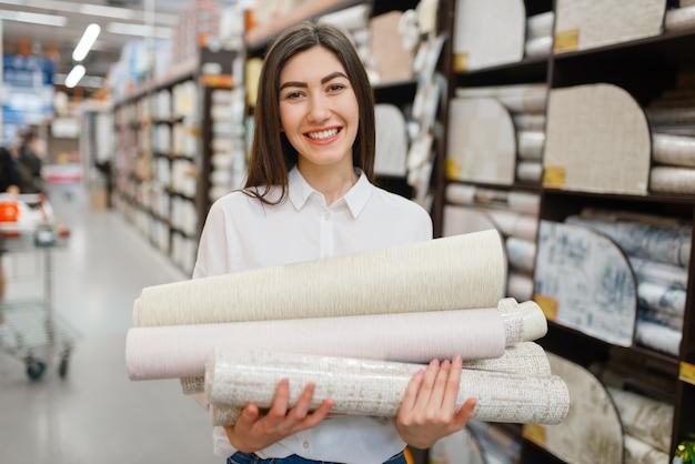 Female customer choosing wallpapers in hardware store.