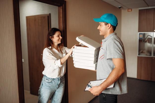 Female customer and delivery boy checks pizza