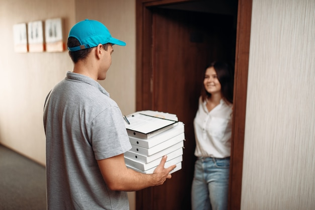 Female customer on doorstep and pizza delivery boy