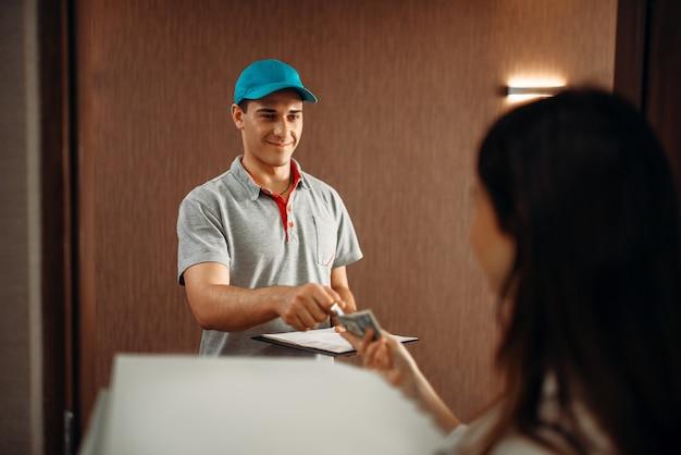 女性のお客様が宅配便業者にチップを渡して、温かいピザをすばやく配達する