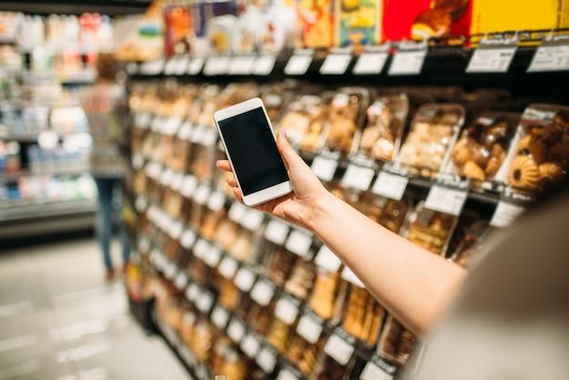 食料品店で携帯電話を持つ女性客の手。食料品や市場、ケーキセクションの女性