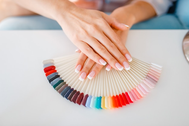Female customer hands and colorful nail varnish palette in beauty shop.
