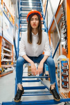 Female customer in helmet sitting on the stairs in hardware store.