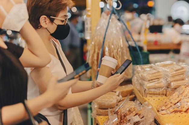 보호 마스크를 쓴 여성 고객은 소매점에서 비접촉 모바일 결제를 합니다.