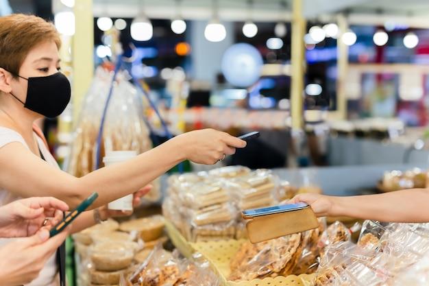 보호 마스크를 쓴 여성 고객은 소매점에서 비접촉 모바일 결제 판매 여성을 만듭니다.