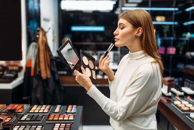 女性客が化粧品店の鏡を見て