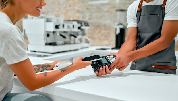 バリスタがクレジットカードを持ってカフェのカウンターで携帯電話で支払いをする女性客