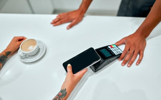 Клиентка-женщина делает оплату через мобильный телефон на стойке в кафе с молодым человеком.