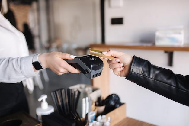 Клиентка-женщина делает беспроводные или бесконтактные платежи с помощью кредитной карты крупным планом человеческих рук