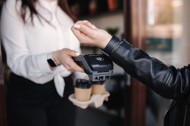 Клиентка женского пола, совершающая беспроводные или бесконтактные платежи с помощью кассира smartwatch, принимающего платеж