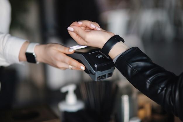 Женщина-клиент, совершающая беспроводные или бесконтактные платежи с помощью умных часов крупным планом рук во время